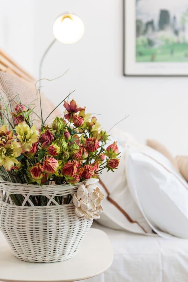 Η διακόσμηση σπιτιών απαριθμεί το άσπρο καλάθι με τα λουλούδια στοκ εικόνες
