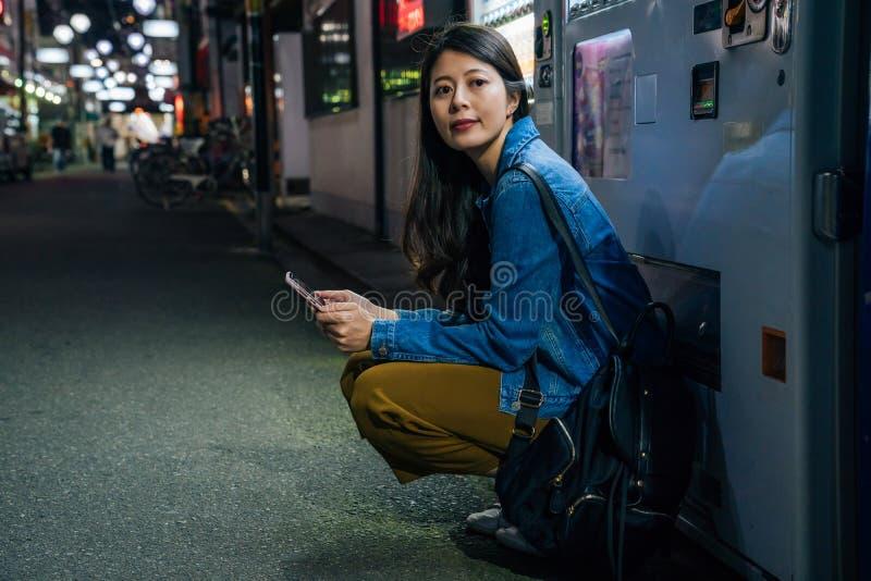 Η ιαπωνική γυναίκα σκύβει κάτω από τη μηχανή πώλησης περιμένοντας το φίλο κομψή κυρία που χρησιμοποιεί την επαφή app κινητών τηλε στοκ εικόνες με δικαίωμα ελεύθερης χρήσης