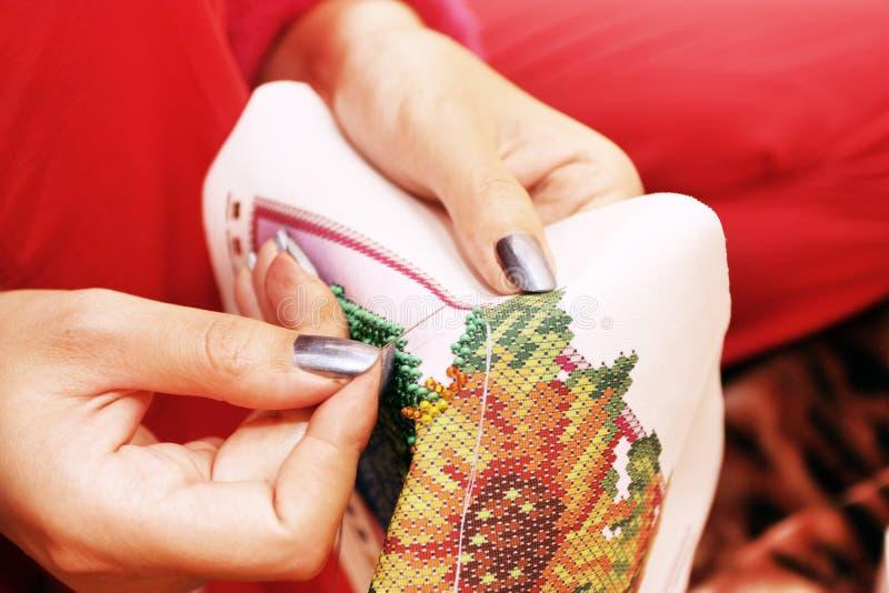 Η διαδικασία κεντητικής στο ύφασμα διακοσμεί τα χέρια με χάντρες στοκ εικόνες