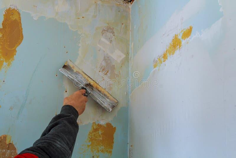 Η διαδικασία putty οι τοίχοι με μεγάλο spatula στοκ εικόνες