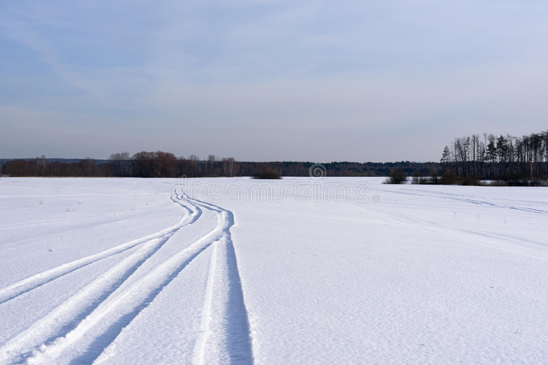 Η διαδρομή σε έναν χιονισμένο τομέα που φεύγει μακρυά στοκ εικόνες