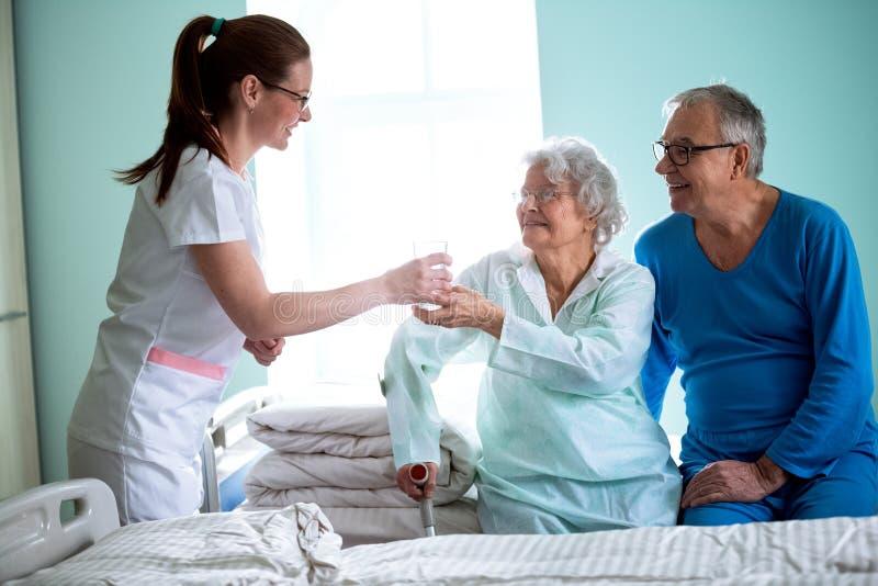 Η ιδιωτική κλινική, νέα προσεκτική νοσοκόμα φέρνει το νερό στη ηλικιωμένη γυναίκα στοκ εικόνες με δικαίωμα ελεύθερης χρήσης