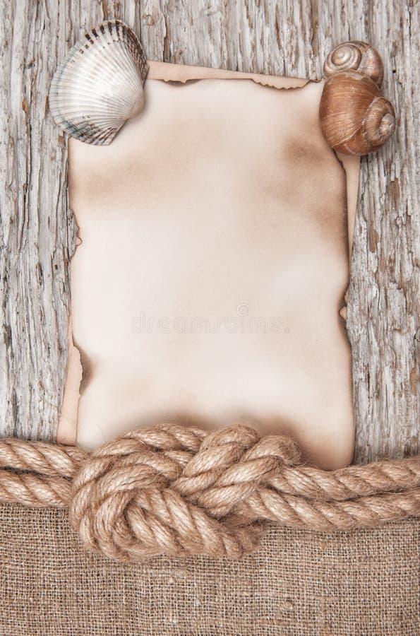 Ηλικίας έγγραφο με το σχοινί σκαφών και θαλασσινά κοχύλια στο παλαιό ξύλο στοκ εικόνα