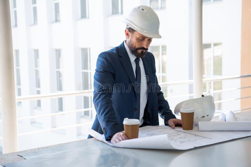 Ηλικίας αρχιτέκτονας στο κοστούμι που εξετάζει τα σχεδιαγράμματα στην περιοχή κατασκευής στοκ εικόνα
