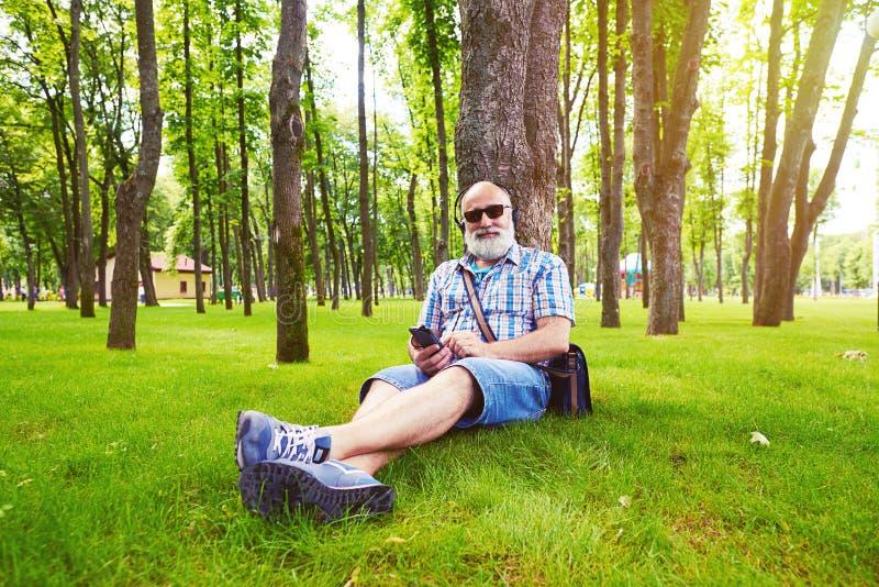 Ηλικίας μοντέρνη συνεδρίαση ατόμων κάτω από το δέντρο και άκουσμα τη μουσική στοκ φωτογραφίες με δικαίωμα ελεύθερης χρήσης