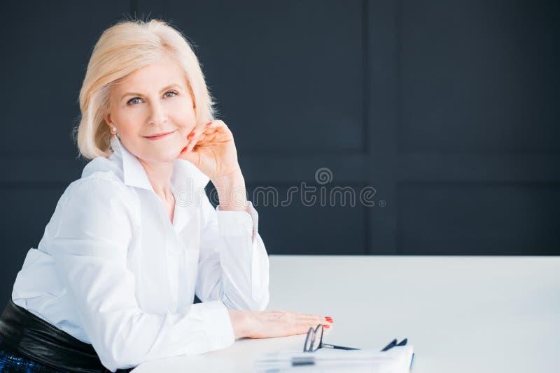 Η ικανοποιημένη ανώτερη γυναίκα χαλάρωσε τον εκτελεστικό χρόνο ανάπαυλας στοκ εικόνα