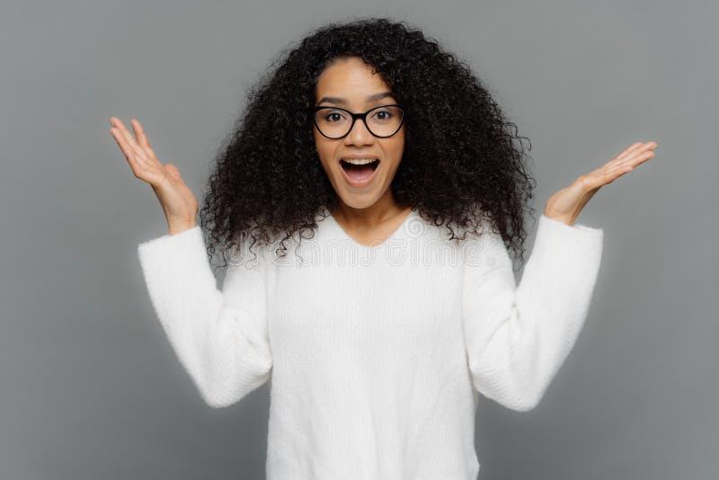 Η ικανοποιημένη γυναίκα αφροαμερικάνων αυξάνει παραδίδει τη χειρονομία του EUREKA, κρατά τους φοίνικες αυξημένο, ευρύ ανοιγμένο σ στοκ φωτογραφίες