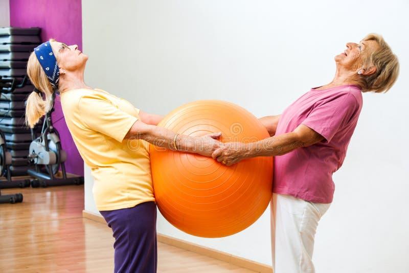 Ηλικιωμένες γυναίκες που τεντώνουν με τη σφαίρα γυμναστικής στοκ φωτογραφίες με δικαίωμα ελεύθερης χρήσης