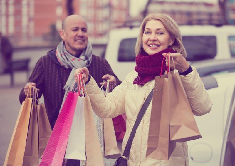 Ηλικιωμένες φέρνοντας αγορές ζευγών και χαμόγελο υπαίθρια στοκ εικόνα με δικαίωμα ελεύθερης χρήσης