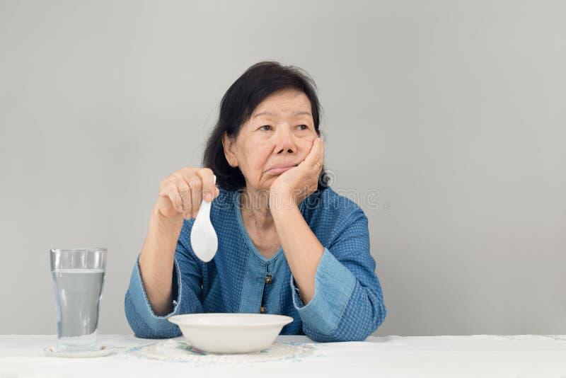 Ηλικιωμένη ασιατική γυναίκα που τρυπιέται με τα τρόφιμα στοκ εικόνες με δικαίωμα ελεύθερης χρήσης