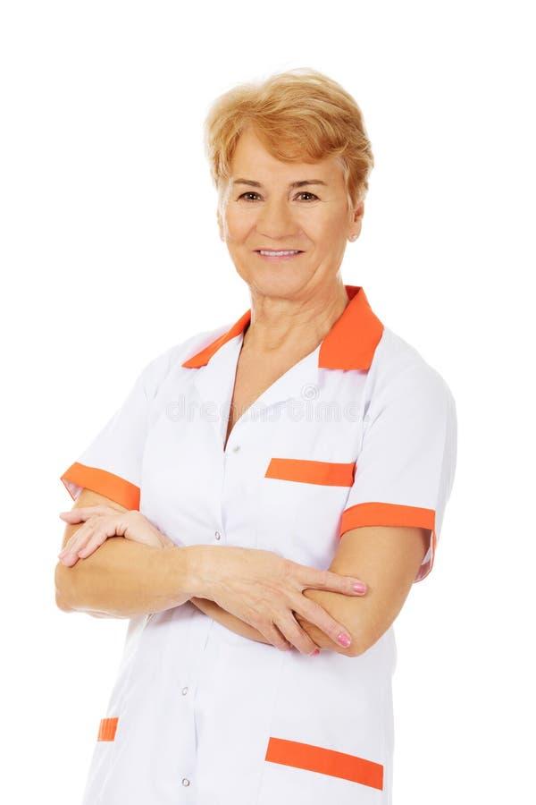 Ηλικιωμένη γιατρός ή νοσοκόμα θηλυκών χαμόγελου με τα διπλωμένα όπλα στοκ φωτογραφία με δικαίωμα ελεύθερης χρήσης