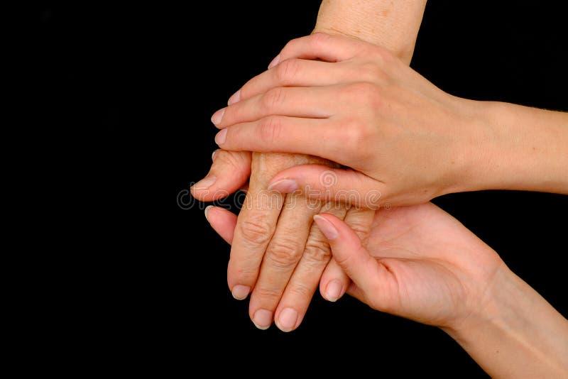Ηλικιωμένη γυναίκα και νέα χέρια εκμετάλλευσης γυναικών από κοινού στοκ φωτογραφία