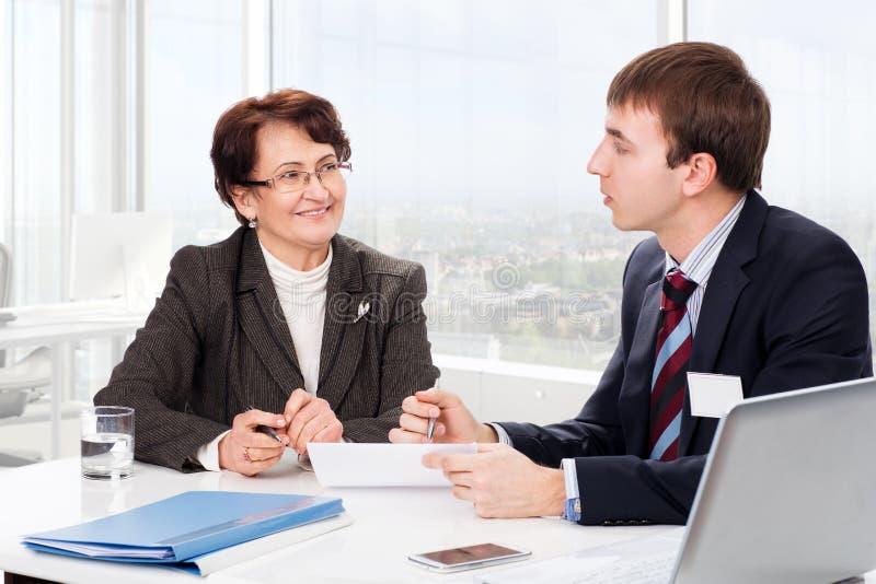 Ηλικιωμένη γυναίκα με έναν οικονομικό σύμβουλο στοκ φωτογραφίες