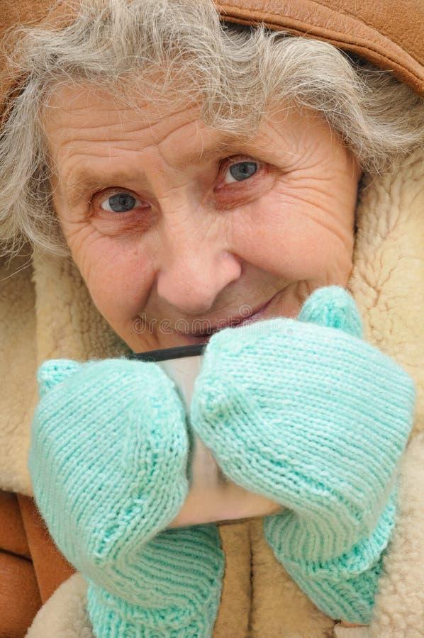 Ηλικιωμένη γυναίκα με την κούπα του καυτού τσαγιού στοκ εικόνες