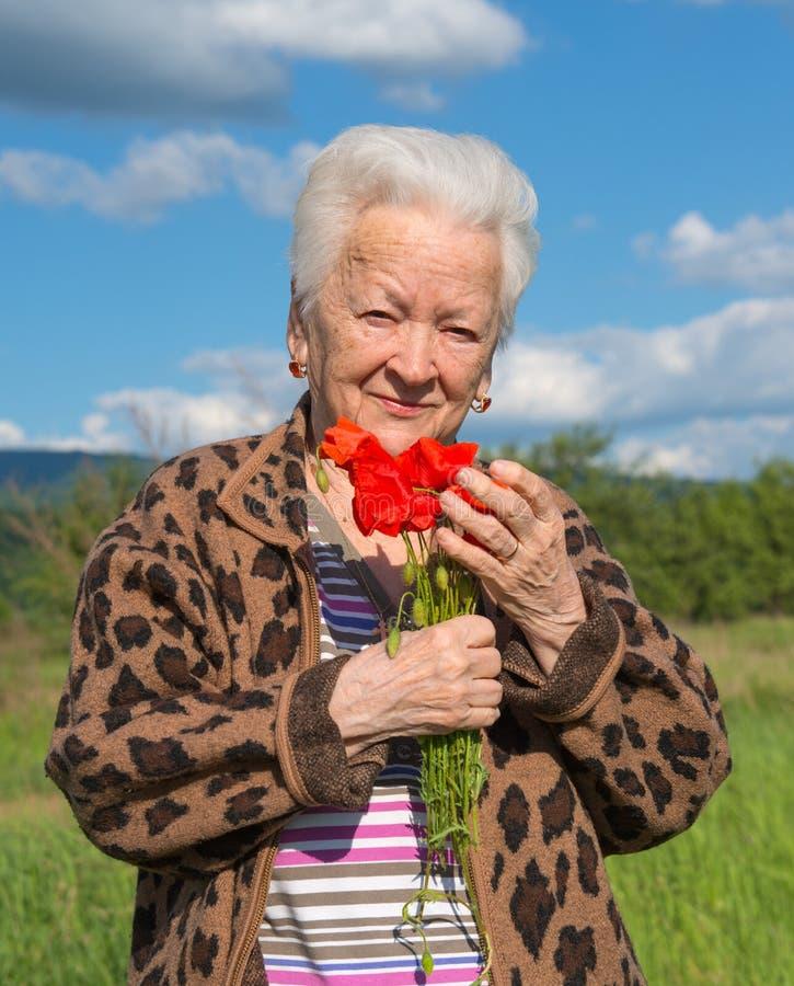 Ηλικιωμένη γυναίκα με τις παπαρούνες στοκ φωτογραφία