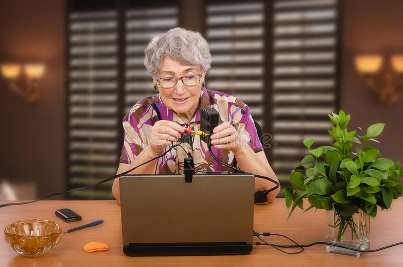 Ηλικιωμένη γυναίκα που αρχίζει να μαθαίνει τη σειρά μαθημάτων υπολογιστών στοκ εικόνα
