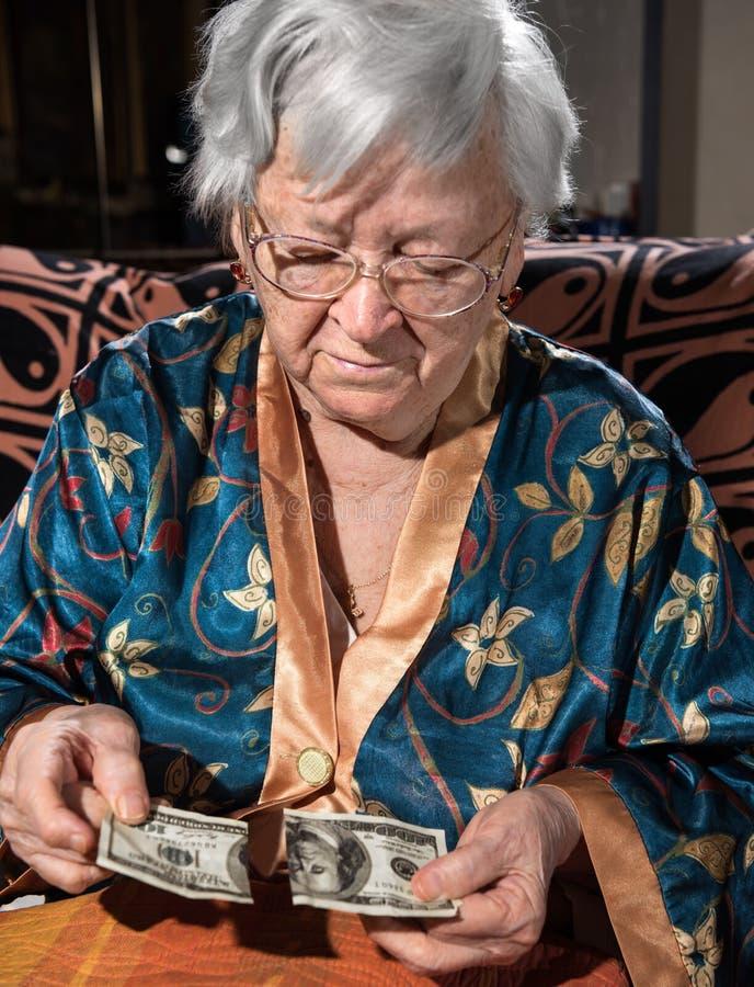 Ηλικιωμένη γυναίκα που εξετάζει το σχισμένο 100 λογαριασμό εκατό δολαρίων στοκ εικόνες με δικαίωμα ελεύθερης χρήσης