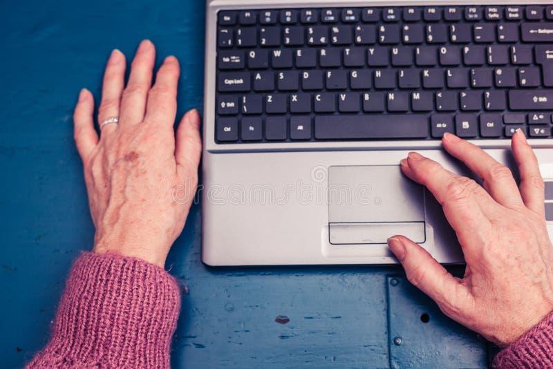 Ηλικιωμένη γυναίκα που εργάζεται στο φορητό προσωπικό υπολογιστή στο σπίτι στοκ φωτογραφίες με δικαίωμα ελεύθερης χρήσης