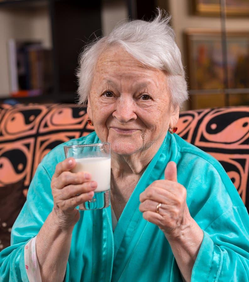 Ηλικιωμένη γυναίκα που κρατά ένα γάλα γυαλιού στοκ φωτογραφία