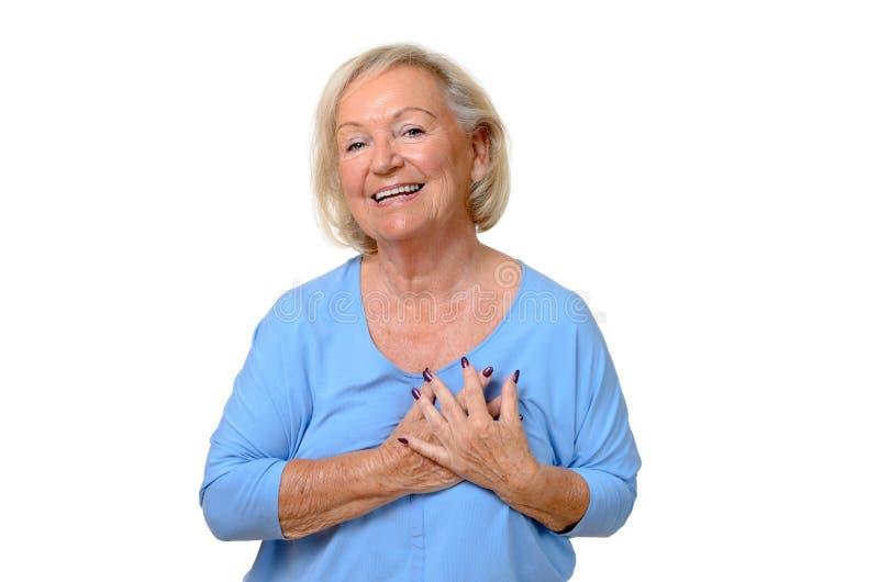 Ηλικιωμένη γυναίκα που κρατά τα χέρια της στην καρδιά της στοκ φωτογραφία