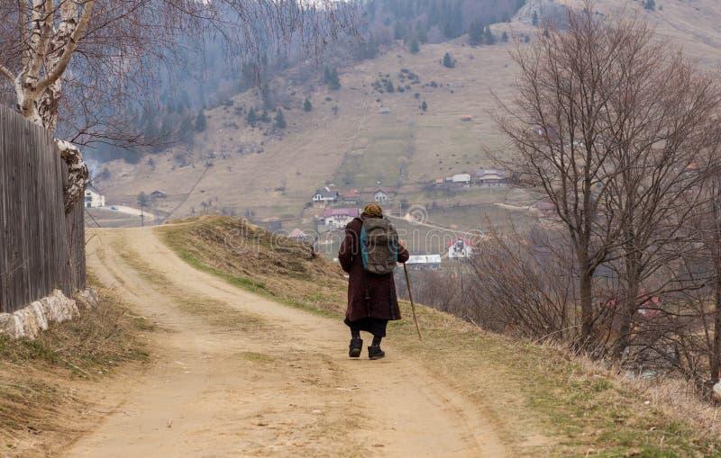 Ηλικιωμένη γυναίκα που περπατά σε έναν δρόμο ορεινών χωριών στοκ εικόνα