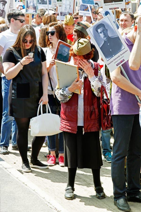 Ηλικιωμένη γυναίκα που φωνάζει πέρα από ένα πορτρέτο των συγγενών στο αθάνατο σύνταγμα ` δράσης ` την ημέρα νίκης στο Βόλγκογκραν στοκ φωτογραφία με δικαίωμα ελεύθερης χρήσης
