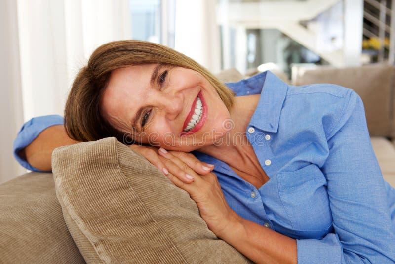 Ηλικιωμένη γυναίκα που χαμογελά στον καναπέ στο σπίτι στοκ εικόνα