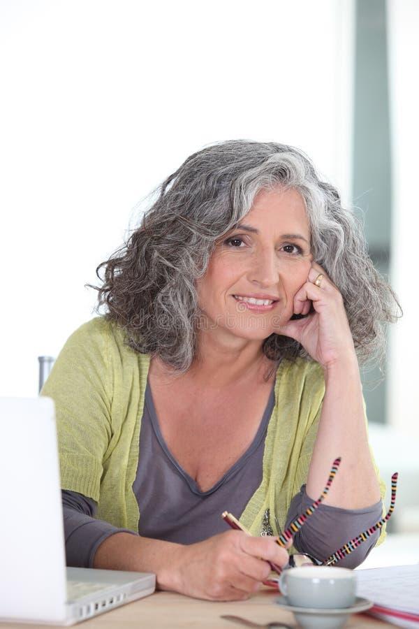 Ηλικιωμένη γυναίκα που χρησιμοποιεί ένα lap-top στοκ εικόνα
