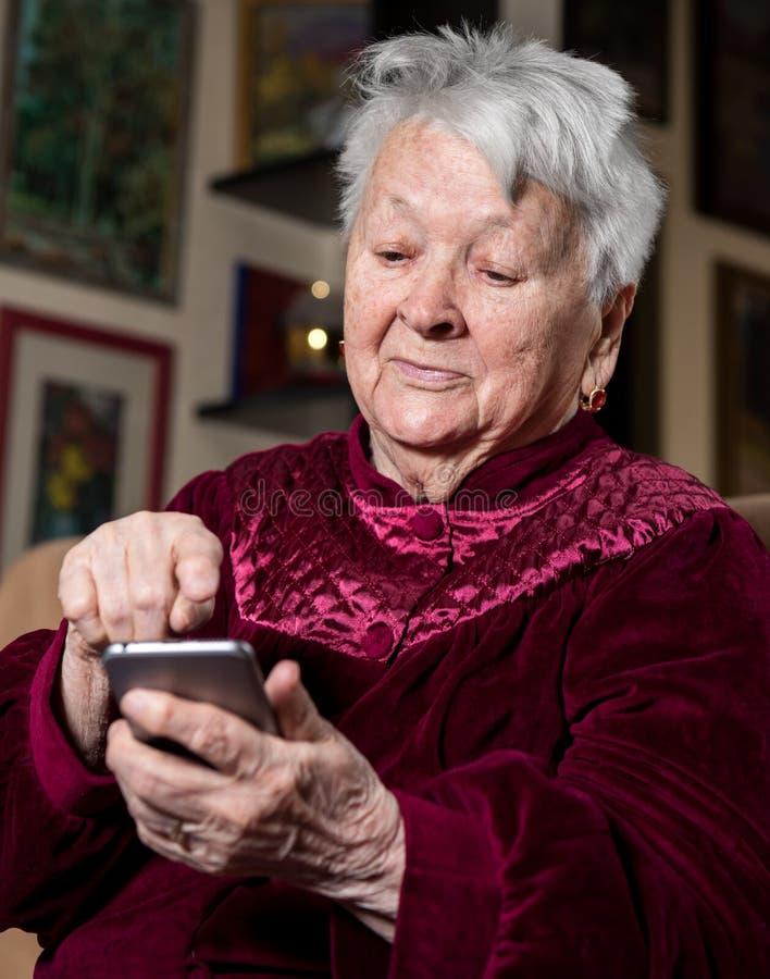Ηλικιωμένη γυναίκα που χρησιμοποιεί το έξυπνο τηλέφωνο στοκ φωτογραφία με δικαίωμα ελεύθερης χρήσης
