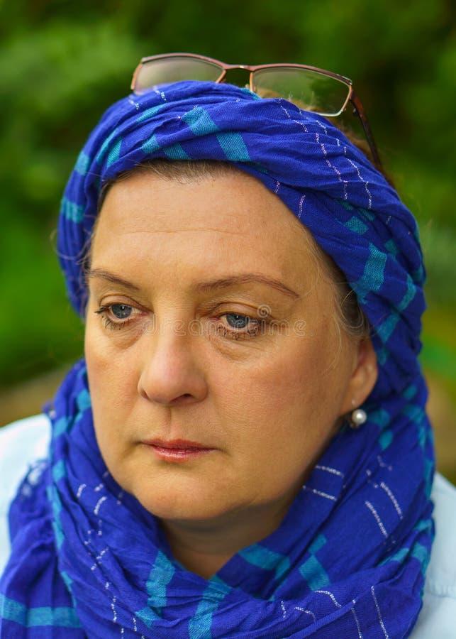 Ηλικιωμένη γυναίκα στη φύση στο μπλε μαντίλι στοκ φωτογραφία με δικαίωμα ελεύθερης χρήσης
