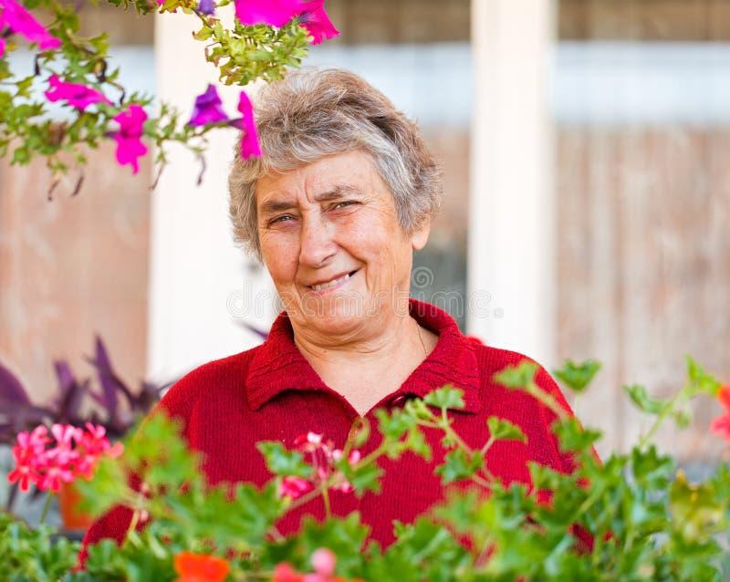 Ηλικιωμένη κυρία με τα λουλούδια στοκ φωτογραφία με δικαίωμα ελεύθερης χρήσης