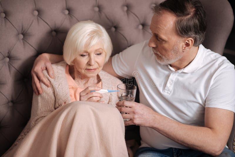 Ηλικιωμένη κυρία που ελέγχει το θερμόμετρο κοντά στο σύζυγο στοκ φωτογραφία με δικαίωμα ελεύθερης χρήσης