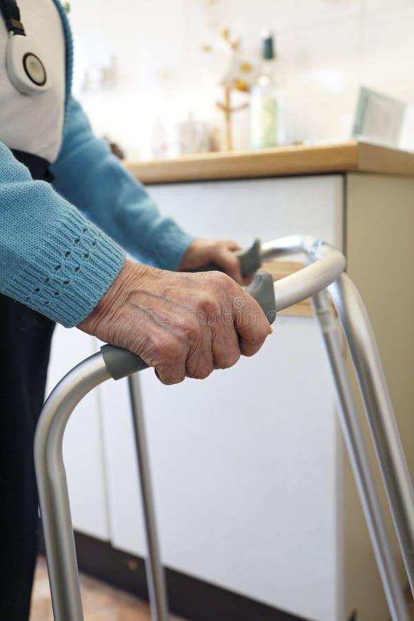 Ηλικιωμένη κυρία που χρησιμοποιεί ένα πλαίσιο περπατήματος στοκ εικόνες
