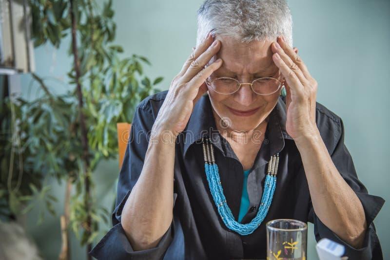 Ηλικιωμένος ακραίος επικεφαλής πόνος γυναικών στοκ εικόνες