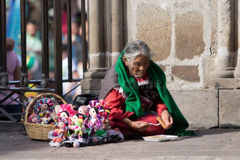 Ηλικιωμένος εγγενής πλανόδιος πωλητής που τρώει τα τρόφιμα καθμένος στο gro στοκ εικόνες με δικαίωμα ελεύθερης χρήσης
