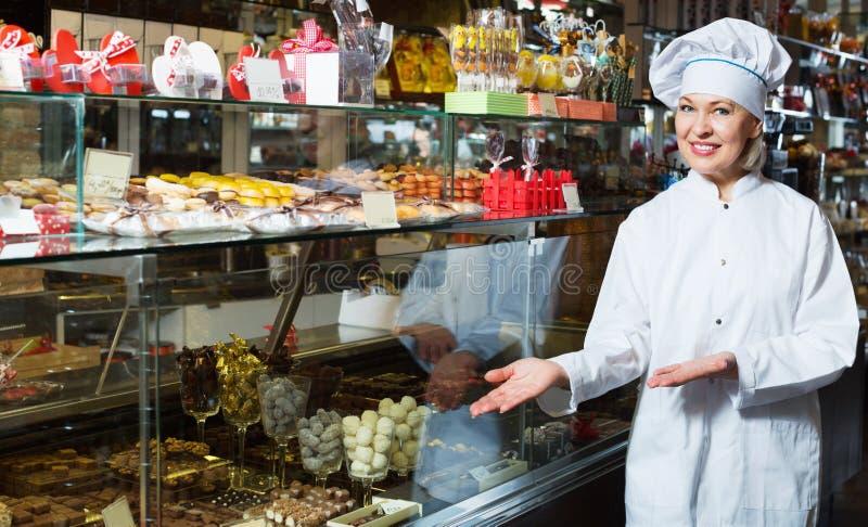Ηλικιωμένος εύθυμος θετικός πωλητής με τις σκοτεινές και άσπρες σοκολάτες στοκ εικόνες