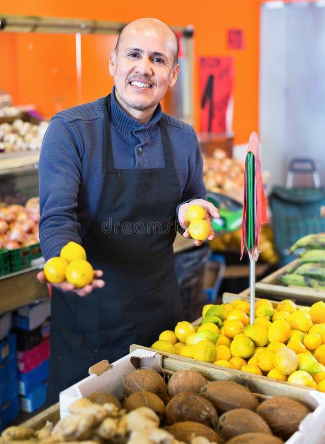 Ηλικιωμένος πωλητής που προσφέρει τα εποχιακά ώριμα φρούτα στο τοπικό παντοπωλείο στοκ εικόνα