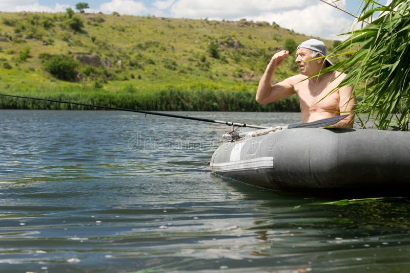 Ηλικιωμένος ψαράς που αλιεύει σε μια λίμνη από μια λέμβο στοκ φωτογραφία με δικαίωμα ελεύθερης χρήσης