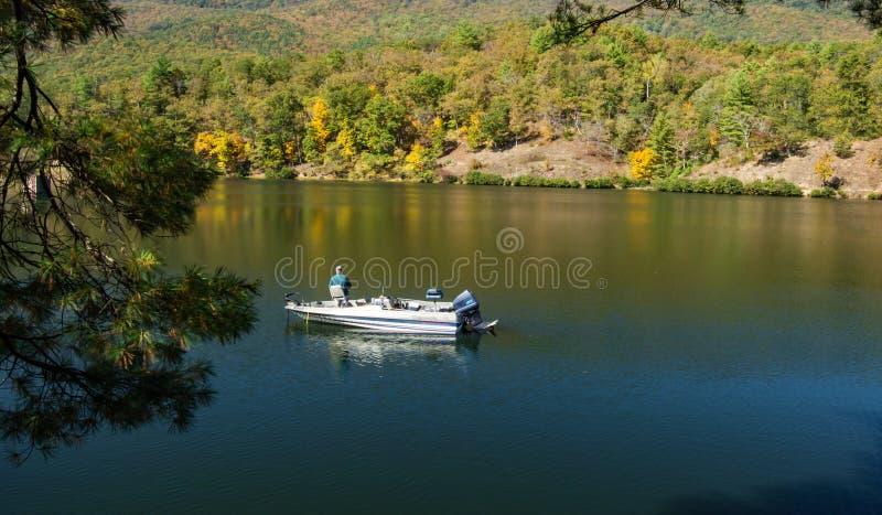 Ηλικιωμένος ψαράς που αλιεύει σε μια λίμνη βουνών στοκ εικόνα