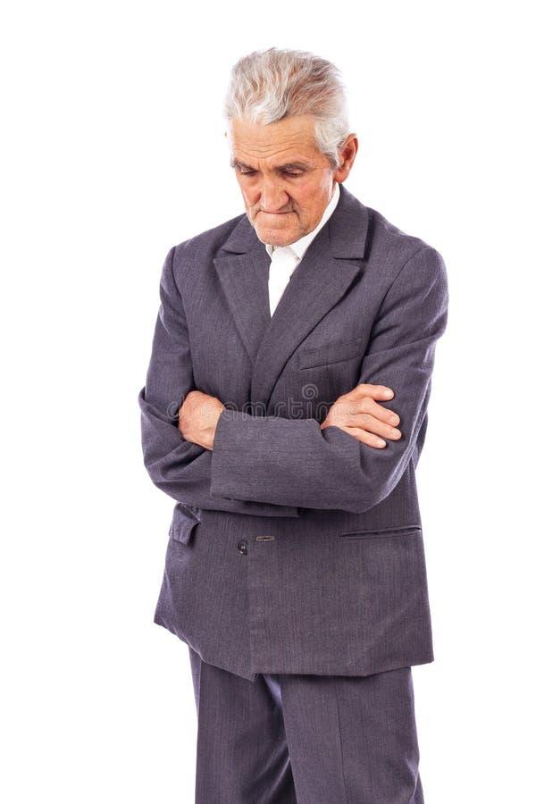 Ηλικιωμένο άτομο με τα όπλα που διπλώνονται κοίταγμα κάτω από χαμένος στη βαθιά σκέψη στοκ φωτογραφίες