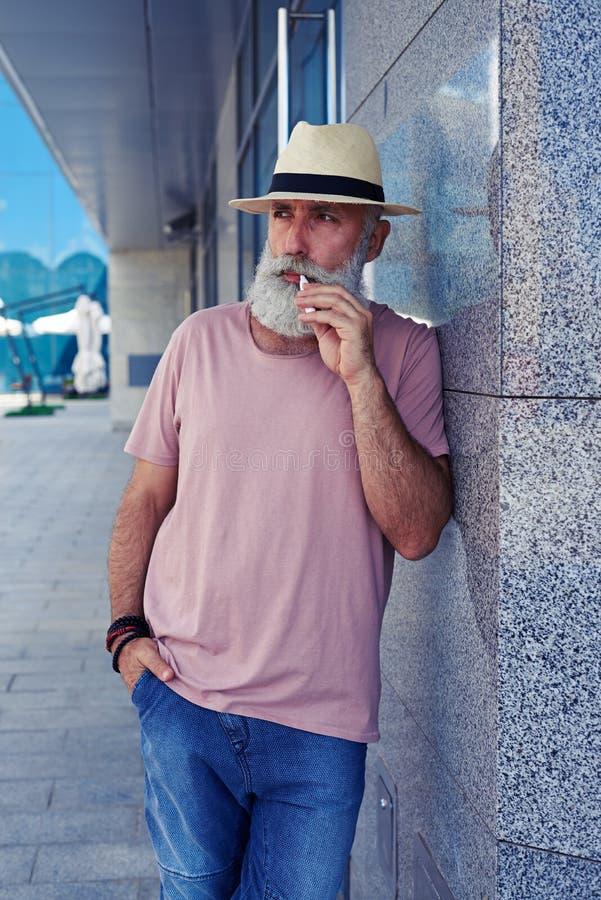 Ηλικιωμένο άτομο με το ηλεκτρο τσιγάρο που στέκεται υπαίθρια στοκ φωτογραφίες με δικαίωμα ελεύθερης χρήσης
