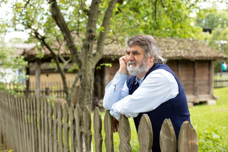 Ηλικιωμένο άτομο μπροστά από το παλαιό σπίτι του στοκ φωτογραφίες με δικαίωμα ελεύθερης χρήσης