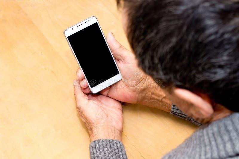 Ηλικιωμένο άτομο που στέκεται με ένα άσπρο κινητό τηλέφωνο στα χέρια στο ξύλο στοκ εικόνα με δικαίωμα ελεύθερης χρήσης