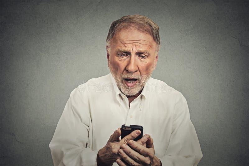 Ηλικιωμένο άτομο, που συγκλονίζεται έκπληκτος από αυτό που βλέπει στο τηλέφωνο κυττάρων του στοκ φωτογραφία με δικαίωμα ελεύθερης χρήσης