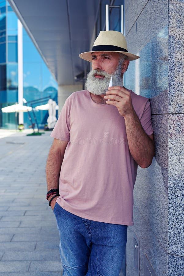 Ηλικιωμένο αρσενικό με το ηλεκτρο τσιγάρο στην πόλη στοκ εικόνες
