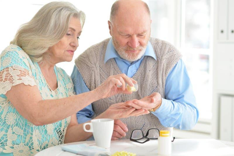 Ηλικιωμένο ζεύγος με τα χάπια στοκ φωτογραφίες