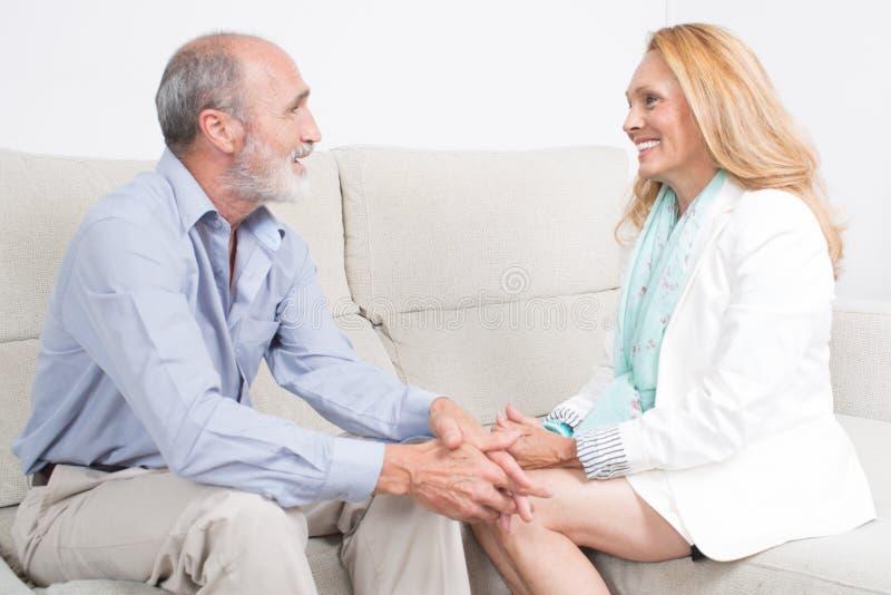 Ηλικιωμένο ζεύγος που μιλά και που χαμογελά στοκ εικόνες