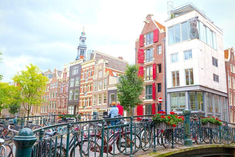 Ηλικιωμένο ζεύγος σε μια γέφυρα του Άμστερνταμ, που περιβάλλεται με το ποδήλατο στοκ εικόνες