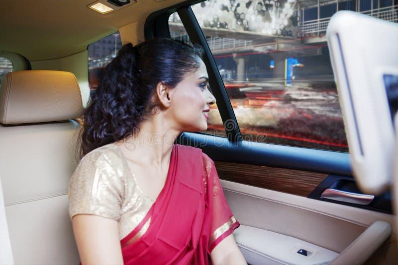Η ινδική γυναίκα κοιτάζει έξω μέσω ενός παραθύρου αυτοκινήτων στοκ εικόνα
