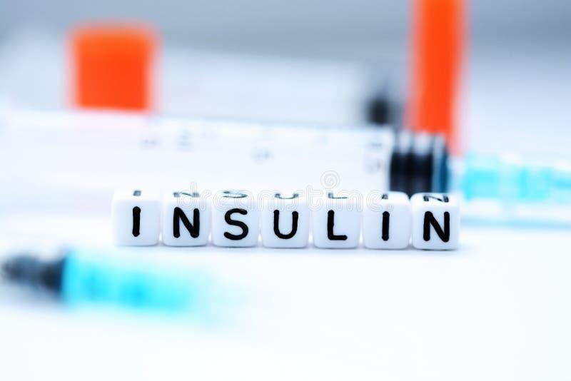 Η ινσουλίνη λέξης που συλλαβίζουν με τις πλαστικές χάντρες επιστολών δίπλα σε μια σύριγγα στοκ φωτογραφίες